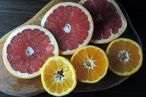 toranja e tangerina em uma placa de madeira foto