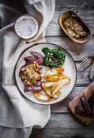 bife com batatas assadas e salada verde sobre fundo de madeira foto