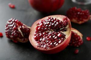 fruta deliciosa romã em fundo preto foto
