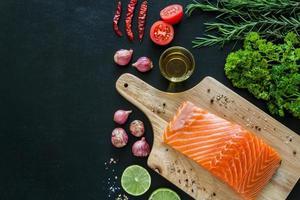 filé de salmão na placa de madeira com enfeite pronto para cozinhar foto