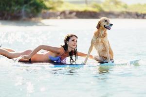 jovem mulher surfando com seu cachorro foto