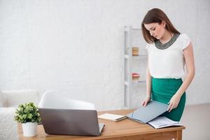 mulher de negócios no escritório em pé perto da mesa com documentos foto