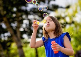 linda criança soprando bolhas foto