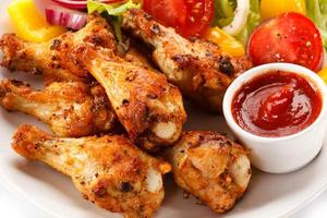 legumes e asas de frango grelhado foto