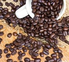 grãos de café e xícara em fundo madeira foto