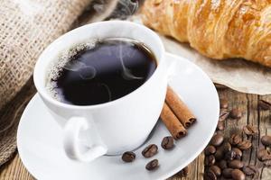 delicioso café com doces em uma mesa de madeira foto