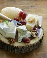 tabuleiro de queijos com queijos variados (parmesão, brie, azul, queijo cheddar)