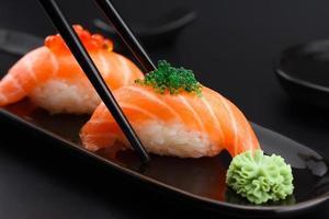nigiri de sushi de salmão em pauzinhos sobre fundo preto