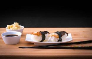 enguia de sushi dois nigiri com molho de soja na mesa de bambu foto