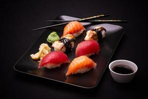 sushi de enguia, salmão e atum com pauzinhos foto
