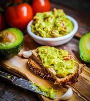 guacamaole com pão e abacate em fundo de madeira rústico foto