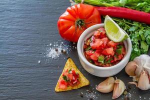 molho de salsa e ingredientes - tomates, cebola, pimentão, alho, limão foto