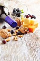 garrafa de vinho tinto, queijo, nozes, castanha de caju e uvas.