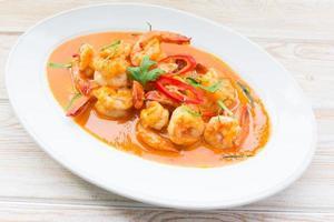 comida tailandesa picante, curry vermelho com camarão na mesa de madeira foto