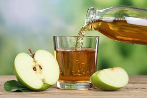 suco de maçã derramando de maçãs verdes em um copo foto