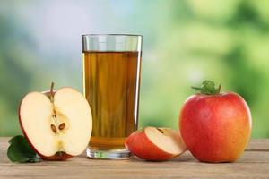 suco de maçã e maçãs vermelhas no verão foto