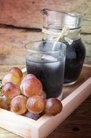 uvas frescas e suco na mesa de madeira foto