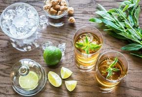 copos de rum no fundo de madeira foto