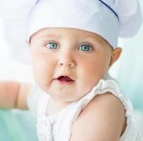 bebê no chef capuz com utensílios de cozinha