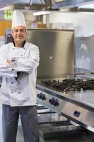 chef sorrindo em pé na cozinha foto