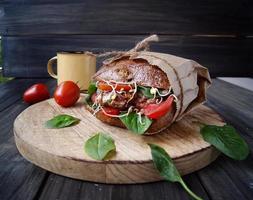 hambúrguer com pão preto e tomate na mesa foto