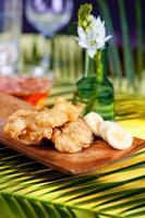 bananas tempura em uma placa de madeira foto