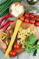 diferentes tipos de macarrão cru em cima da mesa