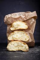 pão quebrado fresco em saco de papel foto