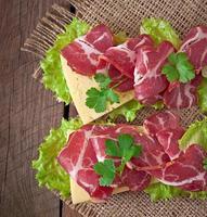 sanduíche grande com carne defumada crua em um fundo de madeira