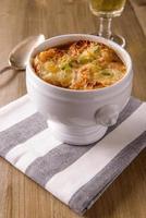 sopa de cebola francesa em uma mesa de madeira foto