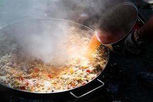 preparando paella com caldo foto