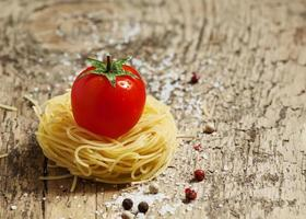 massas secas fidellini e tomates orgânicos frescos foto