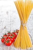 massas alimentícias não cozidas e tomates frescos foto
