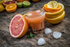 copo de suco e frutas cítricas frescas em madeira rústica foto