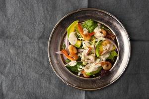 salada de camarão e abacate na placa de metal vintage na toalha de mesa cinza