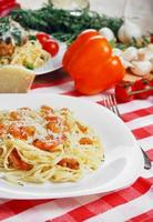 macarrão com camarão e molho na mesa de madeira foto