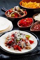 fajitas de carne e frango com pimentões coloridos em tortill foto