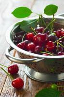 cerejas frescas em uma peneira foto