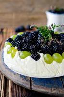 cheesecake com amoras e uvas em uma mesa de madeira velha