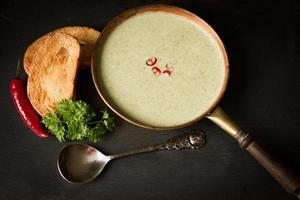 sopa de brócolis com pão torrado em um fundo preto foto