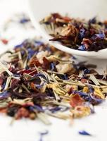 close-up de chá de flores. perto de uma xícara branca e um bule de chá foto