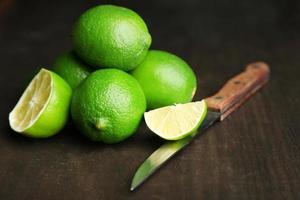 limão suculento fresco na mesa de madeira, em fundo escuro