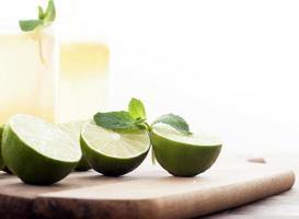 limões frescos e limonada em fundo de madeira