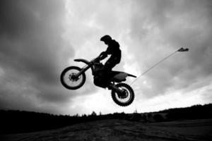 bicicleta da sujeira pulando dunas de areia - sihlouette foto