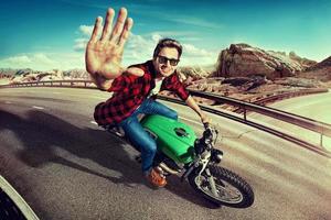 homem andando de moto na estrada. vista do topo foto