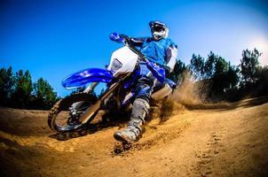 uma vista de ângulo baixo de um motociclista em um percurso de terra