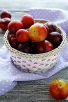ameixas maduras em uma cesta redonda foto