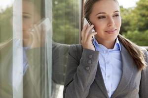 empresária atendendo celular pela porta de vidro foto