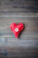 coração de tecido vermelho sobre fundo de madeira foto