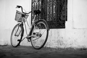 bicicleta cromada vintage com cesto ao lado de uma janela de casa